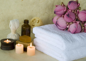 Spa products massage oil with candles and soap with Lotus flowers with background of handmade paper